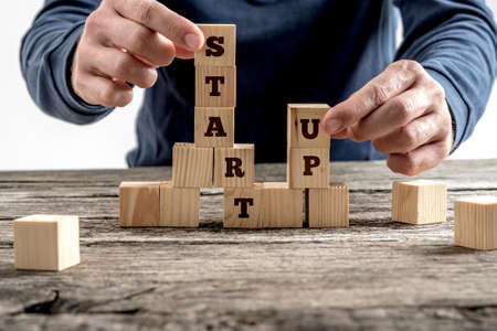 Front view of a businessman arranging wooden cubes in a structure reading Start up. Conceptual of business startup and strategy.