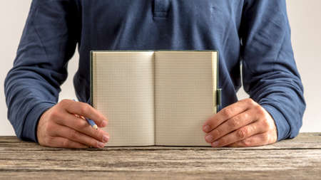 message pad: Front view of a man showing an open blank note pad with pencil in his hand. Copy space ready for your message or sign. Stock Photo