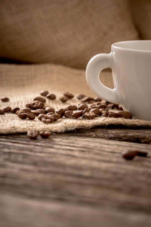 low angles: Low angle view of coffee beans scattered on linen cloth lying on textured wooden desk with a part of white coffee mug. Stock Photo