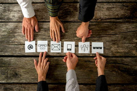 Top view of six people placing white cards with various contact icons in a row on a textured wooden desk. Archivio Fotografico