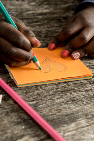 post: Closeup of African-American girl drawing and coloring a heart shape on orange post it paper with a blue colored pencil. Stock Photo