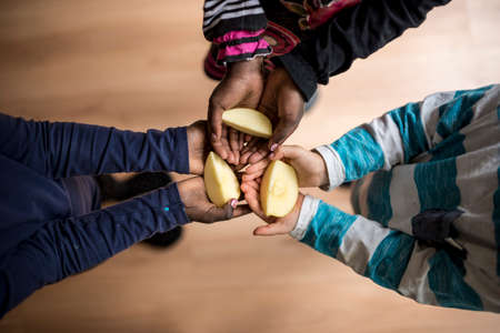 and share: Top view of three kids of mixed races each holding a piece of apple in the palms of their hands.