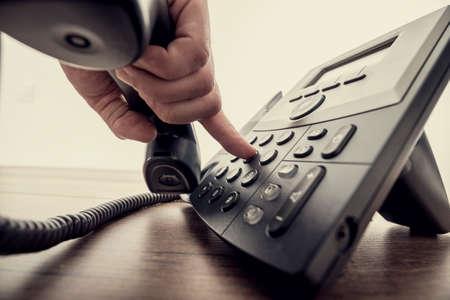 telephone receiver: Closeup of male hand holding telephone receiver and dialing a phone number on a classical black landline telephone. Retro filter effect.