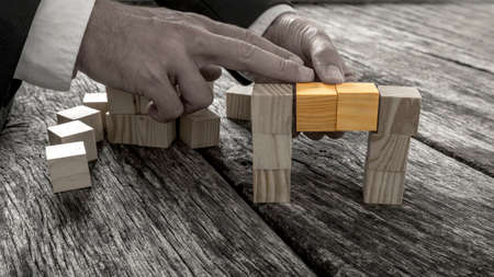 vibrant colour: Closeup of businessman forming a bridge of small wooden blocks in greyscale image with two middle cubes connecting the two sides in standing out in vibrant colour. Stock Photo