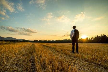 Hombre de negocios en traje elegante con su chaqueta colgada sobre el hombro de pie en el campo de trigo segado mira en la distancia bajo un cielo de la tarde majestuosa con una puesta de sol. Foto de archivo - 54386452