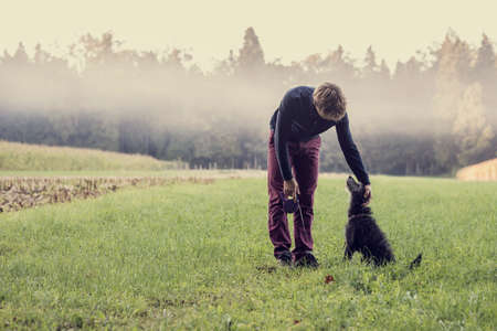 Retro image of a man holding a leash standing in green grassland with forest and mist in background bending down to pat his black dog.