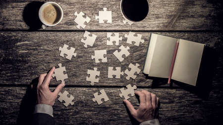 filters: Top view of male hands rearranging puzzle pieces trying to find a solution with blank notepad and cup of coffee on wooden workdesk, vintage effect toned image.