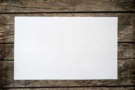 Top view of blank white piece of paper on a textured rustic wooden desk.
