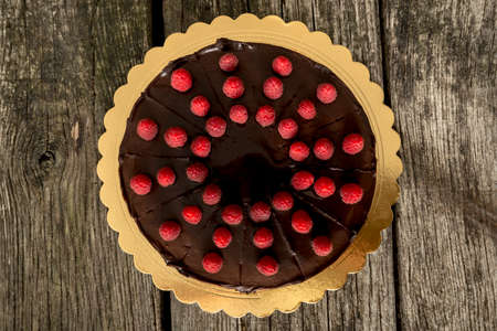 recipe decorated: Top view of delicious whole chocolate cake decorated with fresh ripe raspberries on a golden plate placed on textured rustic wooden desk. Stock Photo