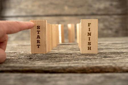 Dominos die zich in U-vorm met het beëindigen van degenen die de woorden beginnen en eindigen en een vinger over het neerslaan van de eerste. Stockfoto