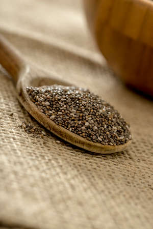 heaping: Closeup view of wooden spoon heaping with dried chia seeds placed on a linen napkin.