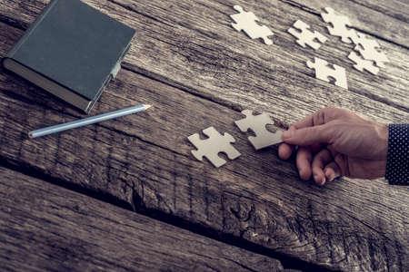 Hand van een zakenman die passen twee puzzelstukjes met blocnote en potlood liggend op zijn gestructureerde houten bureau, vintage effect getinte afbeelding. Stockfoto