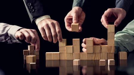 Teamwork en samenwerking concept - vijf mannelijke handen bouwen van een structuur van houten blokken op zwarte bureau met reflectie, afgezwakt retro effect.