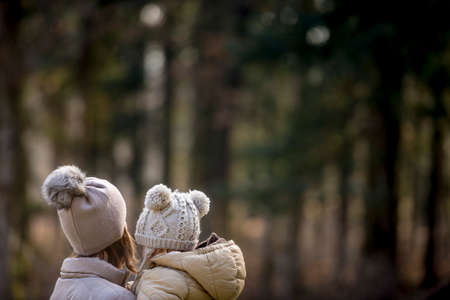 view from behind: View from behind of mother holding her child both wearing warm hats outside in forested area.