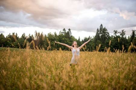 vitality: Young woman enjoying life in beautiful nature standing with her arms outstretched in the middle of autumn meadow under cloudy sky.