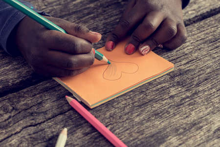 it girl: Closeup of African-American girl with red painted nails drawing and coloring a heart shape on orange post it paper. With a vintage style filter effect.