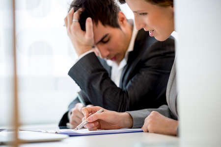 agitated: Business colleagues, man and woman, working at office desk reading a report or document looking a bit stressed and agitated. Focus to her hand. Stock Photo