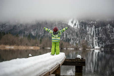 boy kid: Toddler in green winter suit standing at the end of a snow covered pier on a lake with his arms outstretched towards beautiful winter nature.