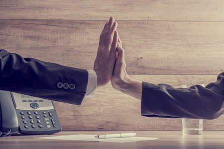 businessman phone: Retro image of business colleagues making high five gesture over a contract or document with a pen lying on it. Conceptual of agreement and cooperation.