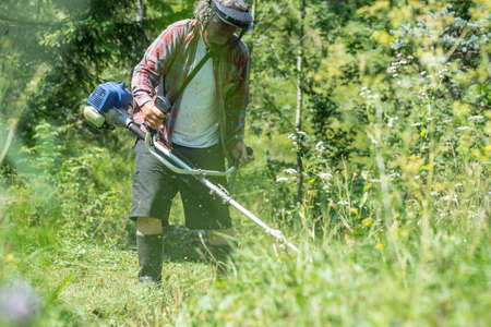 weeds: View through high grass of a man with protective headwear and goggles trimming the lawn with weed eater. Stock Photo