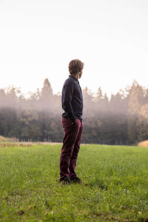Young man standing in green meadow with forest and mist in background turning away from the camera to look into distance.