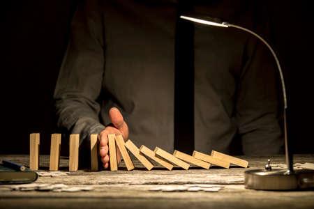 Vista frontal do empresário parando dominó caindo com a mão na mesa de escritório com textura de madeira com uma lâmpada ligada.