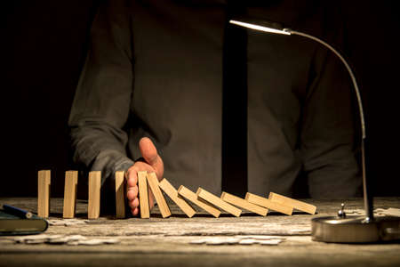 Widok biznesmena zatrzymania spadającego domino z ręką na drewnianym biurku teksturowane z lampą przednia włączony.