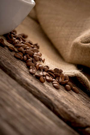 burlap sac: Closeup view of coffee beans scattered on rustic textured wooden desk with burlap sac in background and part of white coffee mug on the left side of the image.
