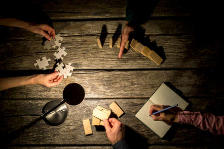 hands work: Top view of male and female business colleagues coworking on a project late at night as they take notes, stop the falling dominos, try to match puzzle pieces and make a construction of wooden pegs.