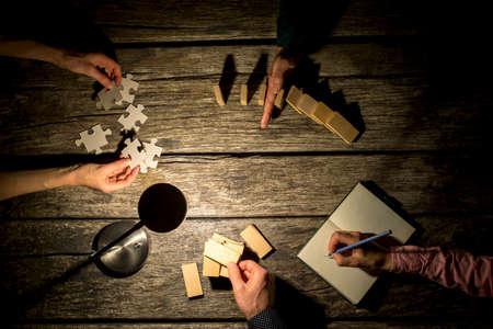 trompo de madera: Vista superior de colegas masculinos y femeninos de coworking en un proyecto a altas horas de la noche, ya que toman notas, detener la caída de fichas de dominó, tratar de igualar las piezas del rompecabezas y hacer una construcción de clavijas de madera.