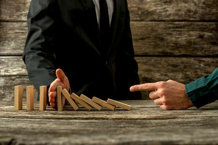 Businessman pointing to falling dominos and his partner stopping them in a conceptual image of cooperation and mentor.