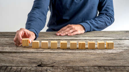 ten empty: Front view of a man placing ten wooden cubes in a row on a desk.