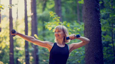 evening out: Retro image of fit young blonde woman working out with dumbbells outside in woodland lit by evening sun rays.