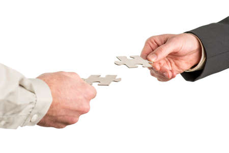 Two hands coming from opposite directions matching two puzzle pieces. Isolated over white background. Stock Photo