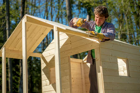Young man using a mallet to fix a nail into a roof of a wooden playhouse for children in a DIY concept.