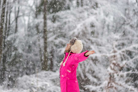mujer alegre: Vista de perfil de mujer joven feliz en pie brillante chaqueta de invierno de color rosa en ventisca de nieve con los brazos extendido ampliamente con árboles cubiertos de nieve blancas en el fondo.