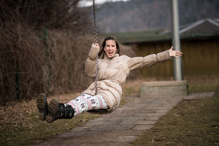 playful: Young woman enjoying life having fun outside in a park on a swing laughing with enjoyment as she flies through the air with one arm wide open.