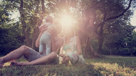 Beautiful family moment - young couple sitting in grass in a park with trees while father holds their toddler child lit by a bright sunlight. With retro filter effect.