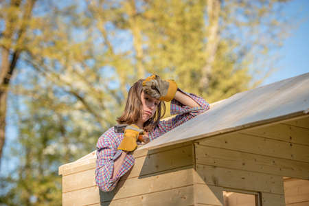 Hard working young woman with exhausted expression holding hand on forehead with hammer working on roof of tree house outdoors.