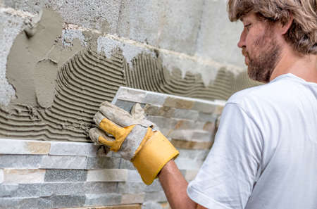 tile adhesive: Closeup of young man with a beard precisely placing an ornamental tile on a wall covered with glue.