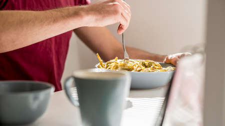 swirling: Closeup of a man swirling spaghetti with pesto sauce with a fork sitting at white desk with coffee mug in front of the pasta plate.