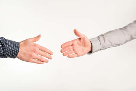 about: Closeup of two businessmen about to shake hands in a handshake over white background.