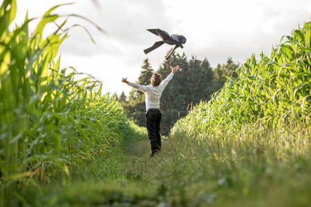 fulfilled: Young businessman celebrating his business freedom and success by throwing his suit jacket in the air standing in grassland between two cornfields.