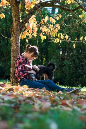 amigos abrazandose: La mujer caucásica joven que se sienta bajo un árbol del otoño que abraza a su perro negro.