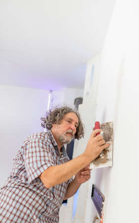 imperfection: Middle-aged man worker, builder or homeowner plastering a white wall preparing it for painting as he repairs a crack or some other imperfection.