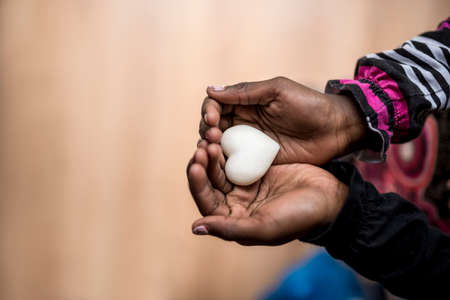 heart hands: Closeup of African-American girl holding a marble made heart shape in her hands with copy space on the left side of the image.
