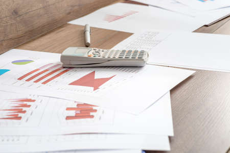 statistical: Paperwork with statistical data, graphs and charts lying on a wooden office desk together with a pen and calculator. Stock Photo