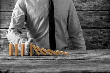 그레이 스케일 이미지는 dominos의 선택적 색상으로 자신의 손으로 떨어지는 도미노를 중지하는 사업가입니다.