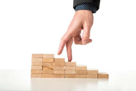 incremento: Mano masculina en traje de negocios caminar sus dedos por una escalera hecha de clavijas de madera, sobre fondo blanco.