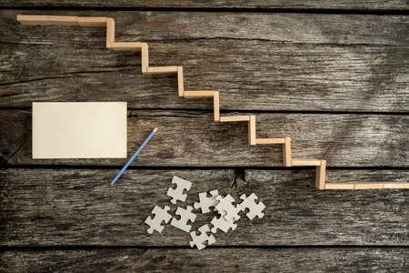 lapiz y papel: Camino al éxito - vista desde arriba de las clavijas de madera que forman una escalera en el escritorio de madera con piezas de un rompecabezas, papel en blanco y un lápiz situada junto a ella.